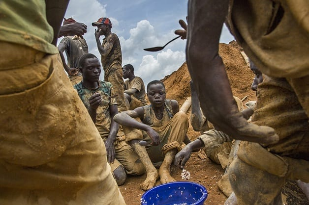 Miners eat lunch from a communal bowl in the mining town of Pluto in Ituri Province. They work here to extract rock and sand from a large pit which has taken over a year to excavate. The miners are made up of many different people from all over Congo who come to seek their fortune. Fixer Pastor Marrion Pudongo +243999836650 marrionudongo@yahoo.fr