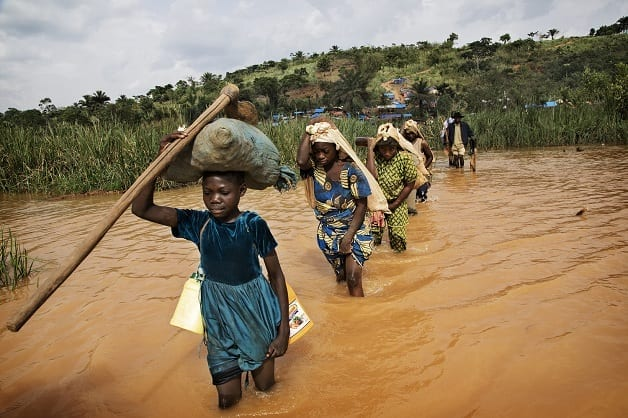 Miners and Traders cross the flooded river to the Gold mine in Baru, Mongbwalu. Recently discovered it has over 3000 miners working there extracting gold. Many of them are soldiers who have deserted and come to look for money. Whole families have relocated to be close to the mine. Fixer Pastor Marrion Pudongo +243999836650 marrionudongo@yahoo.fr